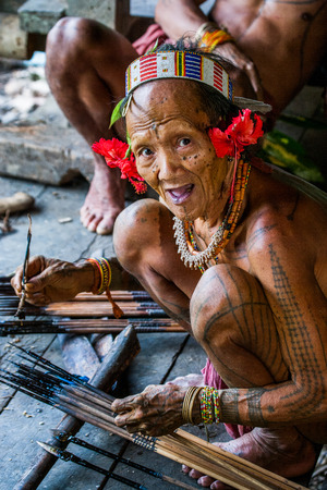 MENTAWAI PEOPLE, WEST SUMATRA, SIBERUT ISLAND, INDONESIA - 16 NOVEMBER 2010: Men Mentawai tribe prepare arrows for hunting.