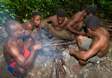 nuova guinea: NEW GUINEA, INDONESIA - 13 JANUARY: Men tribe Yaffi sit around the fire in the jungle. New Guinea Island, Indonesia. January 13th, 2009.