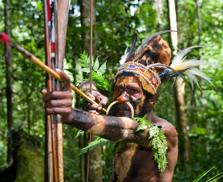 NEW GUINEA, INDONESIA - 13 JANUARY: Warriors tribe Yaffi in war paint with bows and arrows in the cave. New Guinea Island, Indonesia. January 13th, 2009. Editoriali