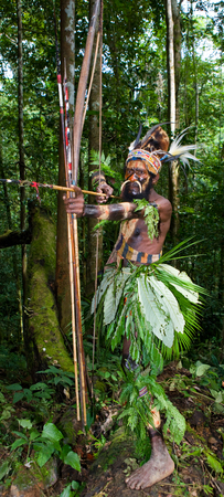 way of life: NEW GUINEA, INDONESIA - 13 JANUARY: Warriors tribe Yaffi in war paint with bows and arrows in the cave. New Guinea Island, Indonesia. January 13th, 2009. Editorial
