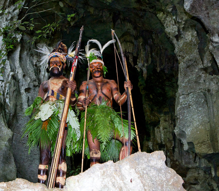ancients: NEW GUINEA, INDONESIA - 13 JANUARY: Warriors tribe Yaffi in war paint with bows and arrows in the cave. New Guinea Island, Indonesia. January 13th, 2009. Editorial
