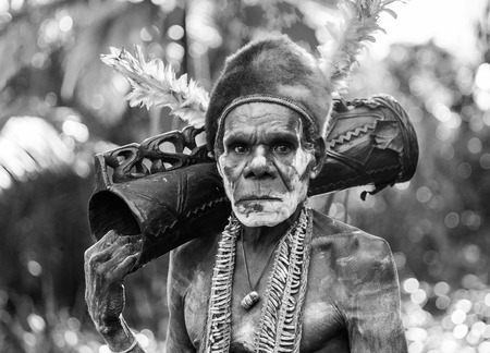 INDONESIA, IRIAN JAYA, ASMAT PROVINCE, JOW VILLAGE - JUNE 12: Portrait of a Warrior Asmat tribe with a ritual drum. Editorial