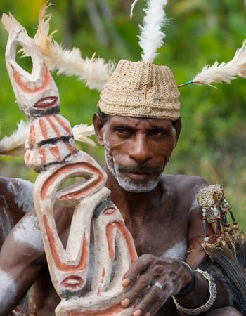 ancients: INDONESIA, IRIAN JAYA, ASMAT PROVINCE, JOW VILLAGE - JUNE 12: Warrior Asmat tribe sits and carves a ritual statue.