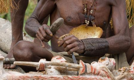 INDONESIA, IRIAN JAYA, ASMAT PROVINCE, JOW VILLAGE - JUNE 12: Warrior Asmat tribe sits and carves a ritual statue.