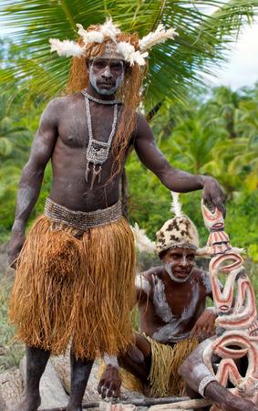 Nuova Guinea: INDONESIA, IRANA JAYA, PROVINCIA DI ASMAT, JOW VILLAGE - 12 GIUGNO: La tribù Warrior Asmat siede e intaglia una statua rituale.