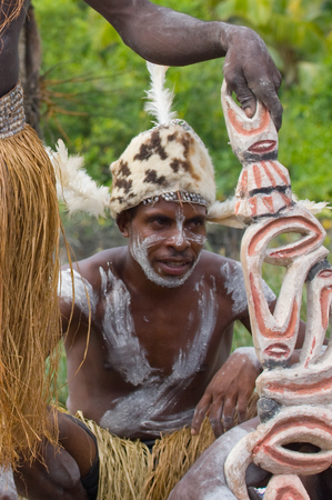 INDONESIA, IRIAN JAYA, ASMAT PROVINCE, JOW VILLAGE - JUNE 12: Warrior Asmat tribe sits and carves a ritual statue.