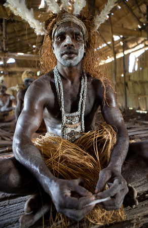 INDONESIA, IRIAN JAYA, ASMAT PROVINCE, JOW VILLAGE - JUNE 12: Warrior Asmat tribe is sitting at home in traditional headdress and war paint.