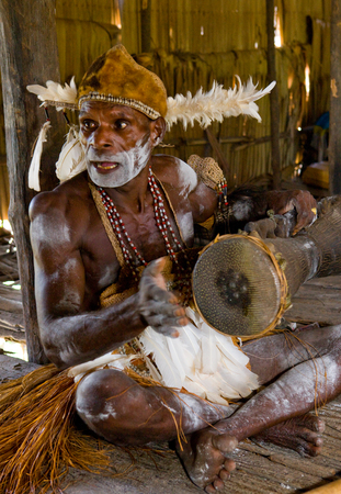 INDONESIA, IRIAN JAYA, ASMAT PROVINCE, JOW VILLAGE - JUNE 12: Men Asmat tribe are sitting at home and play on the drum.