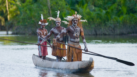 INDONESIA, IRIAN JAYA, ASMAT PROVINCE, JOW VILLAGE - JUNE 12: Warriors Asmat tribe are use traditional canoe.