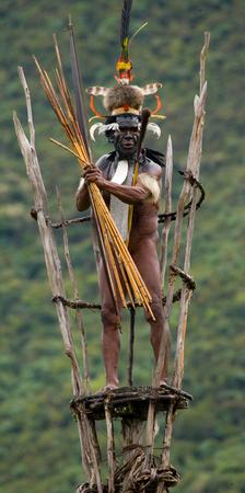 DANI VILLAGE, WAMENA, IRIAN JAYA, NEW GUINEA, INDONESIA - 25 JULY 2009: Dani tribe warrior on the observation tower.