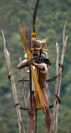 new guinea: DANI VILLAGE, WAMENA, IRIAN JAYA, NEW GUINEA, INDONESIA - 25 JULY 2009: Dani tribe warrior on the observation tower.
