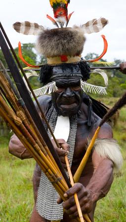 new guinea: DANI VILLAGE, WAMENA, IRIAN JAYA, NEW GUINEA, INDONESIA - 15 MAY 2012: Men Dani tribe shoot an arrow. Editoriali