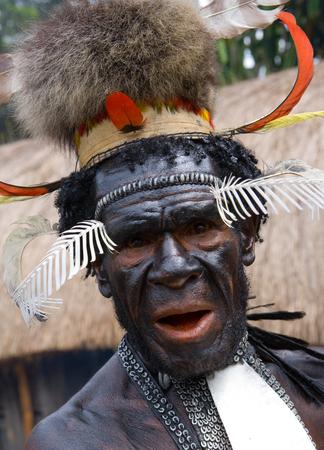 new guinea: DANI VILLAGE, WAMENA, IRIAN JAYA, NEW GUINEA, INDONESIA - 15 MAY 2012: Portrait of Dani tribe in a beautiful headdress made of feathers.