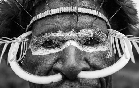 new guinea: DANI VILLAGE, WAMENA, IRIAN JAYA, NEW GUINEA, INDONESIA - 15 MAY 2012: Dani tribe warriors face in a ritual coloring on his face. Editoriali