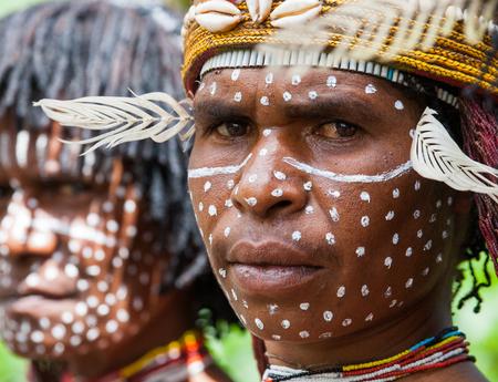 DANI VILLAGE, WAMENA, IRIAN JAYA, NEW GUINEA, INDONESIA - 15 MAY 2012: Portrait of Woman Dani tribe in ritual coloring on the body and face.