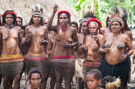 new guinea: DANI VILLAGE, WAMENA, IRIAN JAYA, NEW GUINEA, INDONESIA - 25 JULY 2009: Women Dani tribe sing songs. Editoriali