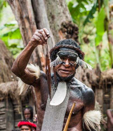 DANI VILLAGE, WAMENA, IRIAN JAYA, NEW GUINEA, INDONESIA - 15 MAY 2012: The chief the tribe Dani shows arrowheads. Editoriali