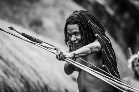 DANI VILLAGE, WAMENA, IRIAN JAYA, NEW GUINEA, INDONESIA - 15 MAY 2012: Woman Dani tribe shoot an arrow. Editorial