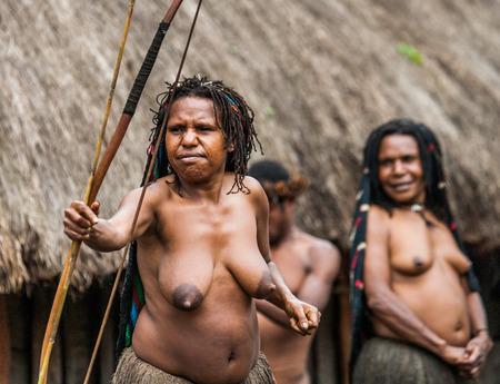 new guinea: DANI VILLAGE, WAMENA, IRIAN JAYA, NEW GUINEA, INDONESIA - 15 MAY 2012: Woman Dani tribe shoot an arrow. Editoriali
