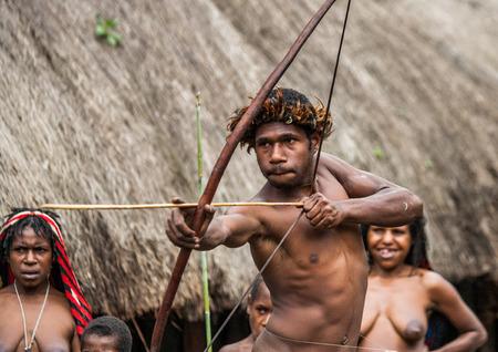 DANI VILLAGE, WAMENA, IRIAN JAYA, NEW GUINEA, INDONESIA - 15 MAY 2012: Men Dani tribe shoot an arrow. Editoriali