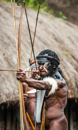dani: DANI VILLAGE, WAMENA, IRIAN JAYA, NEW GUINEA, INDONESIA - 15 MAY 2012: Men Dani tribe shoot an arrow. Editorial