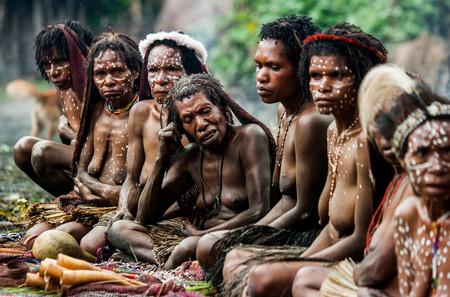 new guinea: DANI VILLAGE, WAMENA, IRIAN JAYA, NEW GUINEA, INDONESIA - 15 MAY 2012: Women Dani tribe sell souvenirs in his village.