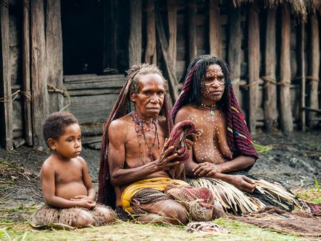 DANI VILLAGE, WAMENA, IRIAN JAYA, NEW GUINEA, INDONESIA - 25 JULY 2009: Woman with children Dani tribe sitting on the ground in the village.