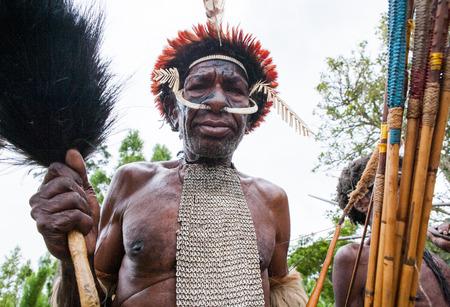 DANI VILLAGE, WAMENA, IRIAN JAYA, NEW GUINEA, INDONESIA - 15 MAY 2012: Portrait of Dani tribe in a beautiful headdress made of feathers.