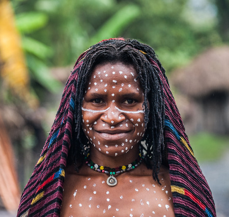 DANI VILLAGE, WAMENA, IRIAN JAYA, NEW GUINEA, INDONESIA - 15 MAY 2012: Portrait of Woman Dani tribe in ritual coloring on the body and face.