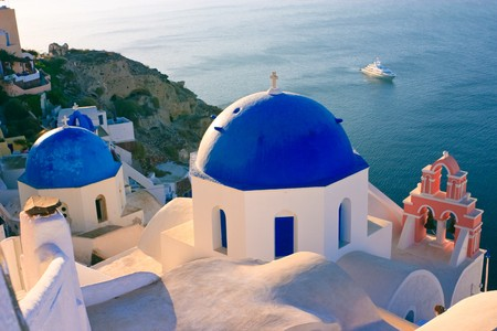 ultramarine blue: The domes of a traditional greek church high on the cliffs in Oia, Santorini, with a large yatch going past on the sea below