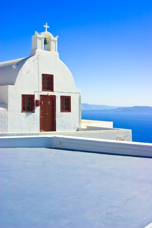 kyklades: A small church or chapel perched on a cliff edge in the town of Oia with a stunning view of the caldera, Santorini, Greece