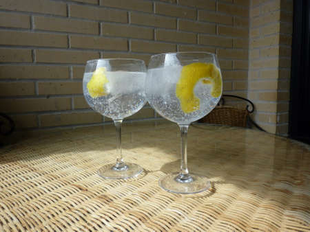 Gin tonic in glass with ice cubes and lime slice. Drink, lemon.
