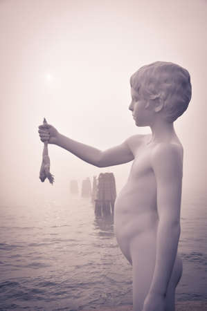 Statue of the Boy with Frog on the edges of the lagoon of Venice