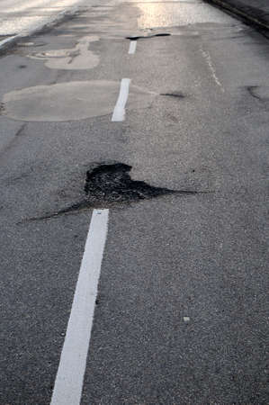 Potholes on a road with white center lines