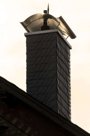 pitched roof: Chimney with shingles and cover plate on a house with pitched roof