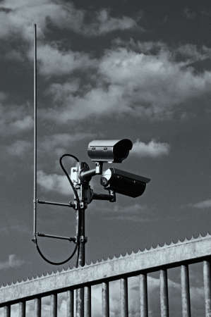 Surveillance cameras behind a serrated iron fence (noise added) Stock Photo - 7110019