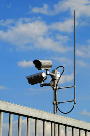 Surveillance camera behind a fence under a blue sky Stock Photo - 7238975