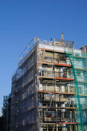 Building with scaffolding and green safety net photo
