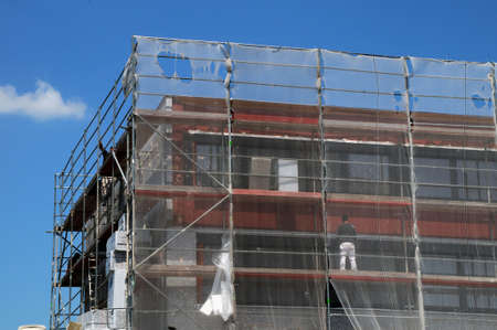 Building with scaffolding and a white transparent safety net