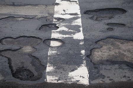 scheidingslijnen: Kuilen beschadigd weg met gaten en een witte scheidslijn