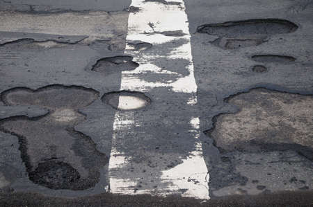 Potholes Damaged road with potholes and a white dividing line
