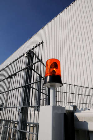 deter: Flashing light at factory Factory building with flashing light and iron fence