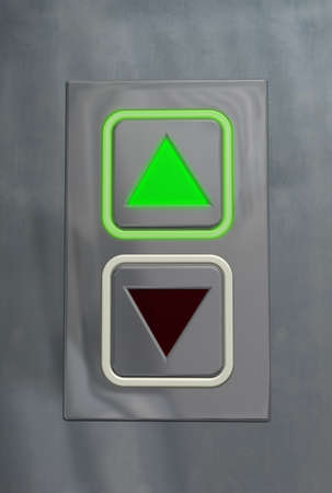 command button: Elevator button upward Elevator information plate in upward position with a shining green pilot lamp Stock Photo