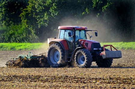 Agricultural work Tractor with cultivation equipment working at a farmland Stok Fotoğraf