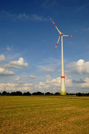 Wind turbine Modern wind turbine in white and red under a blue sky  photo