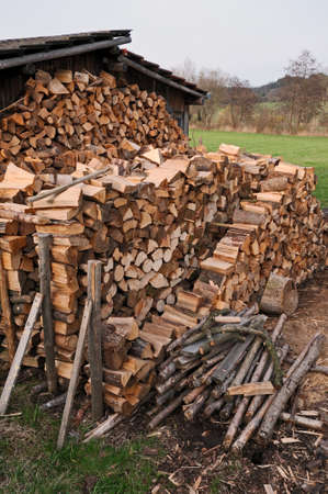woodpile: Hut and firewood Old weathered wooden hut and a stack of cut firewood