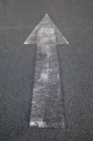 Arrow on asphalt A white arrow on a road photo