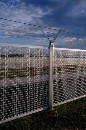 delimit: Metal fence Part of a metal grid fence with barbed wire at the top