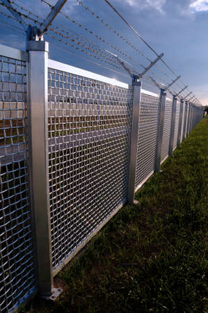 private security: Metal fence Part of a metal grid fence with barbed wire at the top