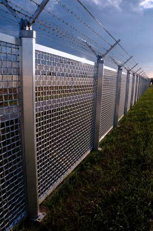 penitenciaria: Parte de metal cerca de una valla de rejilla metálica con alambre de púas en la parte superior